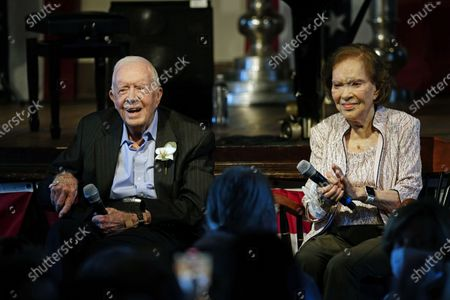 Former President Jimmy Carter and his wife former first lady Rosalynn Carter sit together during a reception to celebrate their 75th wedding anniversary, in Plains, Ga