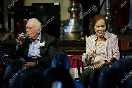 Former President Jimmy Carter sips champagne as his wife former first lady Rosalynn Carter speaks during a reception to celebrate their 75th wedding anniversary, in Plains, Ga