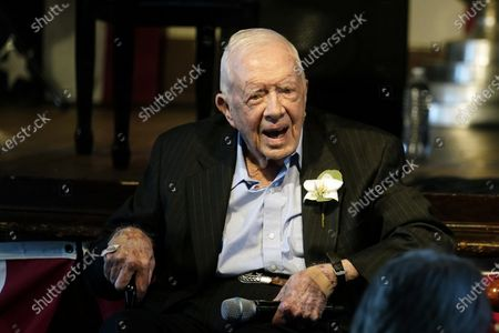 Former President Jimmy Carter reacts as his wife Rosalynn Carter speaks during a reception to celebrate their 75th wedding anniversary, in Plains, Ga