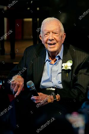 Former President Jimmy Carter smiles as his wife former first lady Rosalynn Carter speaks during a reception to celebrate their 75th wedding anniversary, in Plains, Ga