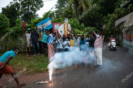 Indian soccer fans garland a cut out photograph of Argentina's Lionel Messi and light firecrackers after Argentina won the Copa America title as they celebrate in Kochi, Kerala state, India