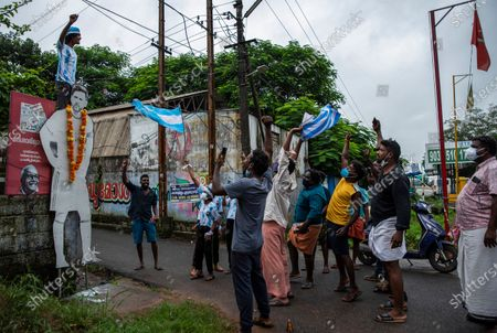 Indian soccer fans garland a cut out photograph of Argentina's Lionel Messi and celebrate after Argentina won the Copa America title in Kochi, Kerala state, India