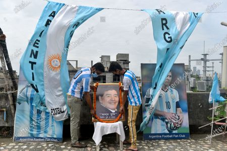 Members of an Argentina's national football team fan club places a portrait of late Argentine football legend Diego Maradona in a rooftop ahead of the Copa America final match between Argentina and Brazil, Kolkata, India, 10 July, 2021.