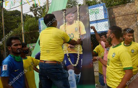 A Brazilian fan puts a flower garland over a photo of Neymar (a professional footballer) ahead of the Copa America final match between Argentina and Brazil, Kolkata, India, 10 July, 2021.
