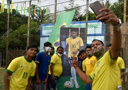 Brazilian takes a selfie picture in front of a photo of Neymar (a professional footballer) ahead of the Copa America final match between Argentina and Brazil, Kolkata, India, 10 July, 2021.
