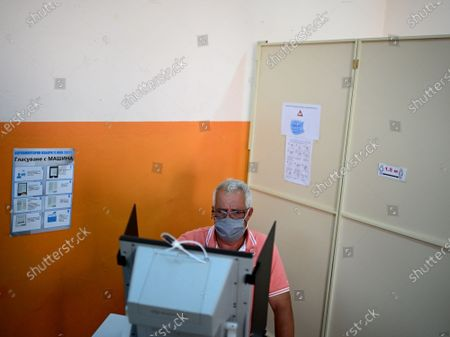 A man casts his vote using a voting machine at a polling station during the country's parliamentary elections in Sofia, Bulgaria, 11 July 2021. Until the polls close at 8:00 p.m. (5:00 p.m. GMT), voters will be able to choose between 23 parties and alliances, seven fewer than the previous 04 April legislatures, to form the new 240-seat Parliament. Victory will be contested by the conservatives of the Bulgarian Citizens for European Development (GERB), led by former Prime Minister Boyko Borissov, and by There Is Such a People, a political party recently founded by singer and television host Slavi Trifonov.