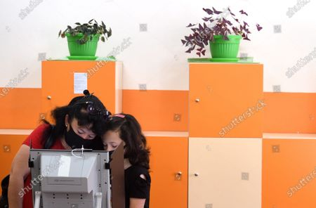 A mother with her daughter casts her vote using a voting machine at a polling station during the country's parliamentary elections in Sofia, Bulgaria, 11 July 2021. Until the polls close at 8:00 p.m. (5:00 p.m. GMT), voters will be able to choose between 23 parties and alliances, seven fewer than the previous 04 April legislatures, to form the new 240-seat Parliament. Victory will be contested by the conservatives of the Bulgarian Citizens for European Development (GERB), led by former Prime Minister Boyko Borissov, and by There Is Such a People, a political party recently founded by singer and television host Slavi Trifonov.