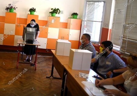 A woman (L) casts her vote using a voting machine at a polling station during the country's parliamentary elections in Sofia, Bulgaria, 11 July 2021. Until the polls close at 8:00 p.m. (5:00 p.m. GMT), voters will be able to choose between 23 parties and alliances, seven fewer than the previous 04 April legislatures, to form the new 240-seat Parliament. Victory will be contested by the conservatives of the Bulgarian Citizens for European Development (GERB), led by former Prime Minister Boyko Borissov, and by There Is Such a People, a political party recently founded by singer and television host Slavi Trifonov.