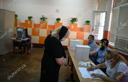 People cast their vote at a polling station during the country's parliamentary elections in Sofia, Bulgaria, 11 July 2021. Until the polls close at 8:00 p.m. (5:00 p.m. GMT), voters will be able to choose between 23 parties and alliances, seven fewer than the previous 04 April legislatures, to form the new 240-seat Parliament. Victory will be contested by the conservatives of the Bulgarian Citizens for European Development (GERB), led by former Prime Minister Boyko Borissov, and by There Is Such a People, a political party recently founded by singer and television host Slavi Trifonov.