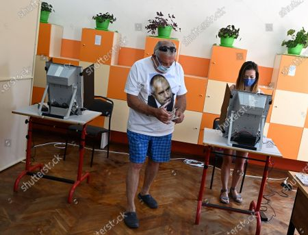 A man (L) wearing a t-shirt with an image of Bulgarian former prime minister Boyko Borissov, the leader of the GERB party, casts his vote at a polling station during the country's parliamentary elections in Sofia, Bulgaria, 11 July 2021. Until the polls close at 8:00 p.m. (5:00 p.m. GMT), voters will be able to choose between 23 parties and alliances, seven fewer than the previous 04 April legislatures, to form the new 240-seat Parliament. Victory will be contested by the conservatives of the Bulgarian Citizens for European Development (GERB), led by former Prime Minister Boyko Borissov, and by There Is Such a People, a political party recently founded by singer and television host Slavi Trifonov.