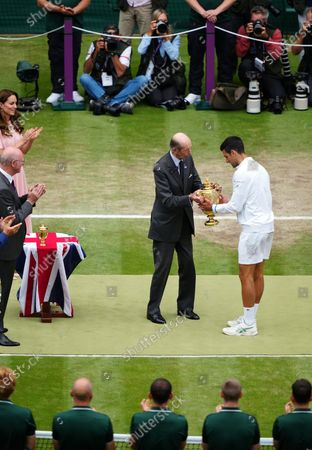 Novak Djokovic is presented with the trophy by The Duke of Kent after victory in the Gentlemen's Singles final