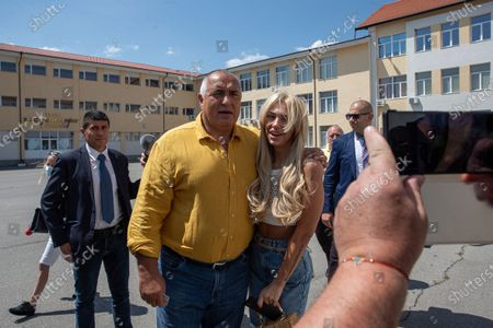 Bulgarian former prime minister Boyko Borissov takes a picture with a fan after voting in parliamentary elections in the town of Bankya near capital Sofia, Bulgaria on . Bulgarians are voting in a snap poll on Sunday after a previous election in April produced a fragmented parliament that failed to form a viable coalition government. Latest opinion polls suggest that the rerun could produce similar results but also a further drop in support for former Prime Minister Boyko Borissov's GERB party, after the current caretaker government made public allegations of widespread corruption during his rule