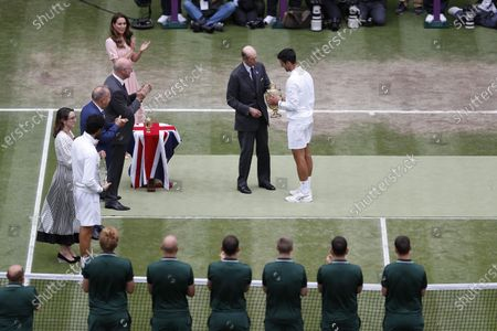 Novak Djokovic (R) of Serbia is presented the trophy by Britain's Prince Edward, Duke of Kent (L) after winning the men's final against Matteo Berrettini of Italy at the Wimbledon Championships, Wimbledon, Britain 11 July 2021.