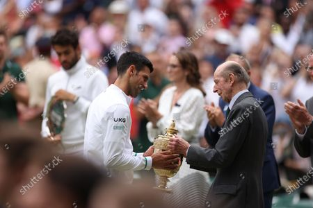 Novak Djokovic (L) of Serbia is presented the trophy by Britain's Prince Edward, Duke of Kent (R) after winning the men's final against Matteo Berrettini of Italy at the Wimbledon Championships, Wimbledon, Britain 11 July 2021.