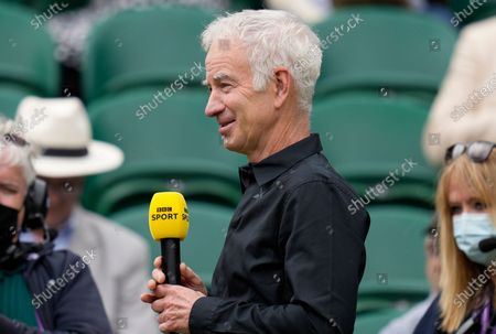 Former Wimbledon champion John McEnroe gives a TV interview ahead of the start of the men's singles final between Serbia's Novak Djokovic and Italy's Matteo Berrettini on day thirteen of the Wimbledon Tennis Championships in London