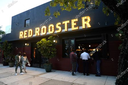 People arrive at the Red Rooster restaurant owned by celebrity chef Marcus Samuelsson, in the Overtown neighborhood in Miami