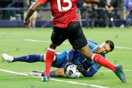 Mexico goalkeeper Alfredo Talavera (1) makes a save in front of Trinidad and Tobago midfielder Reon Moore during the second half of a CONCACAF Gold Cup Group A soccer match against Trinidad and Tobago in Arlington, Texas