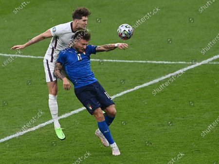 Italy's Ciro Immobile, right, duels for the ball with England's John Stones during the Euro 2020 final soccer match between Italy and England at Wembley stadium in London