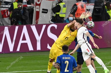 Italy's goalkeeper Gianluigi Donnarumma, left, makes a save in front of England's John Stones during the Euro 2020 final soccer match between Italy and England at Wembley stadium in London