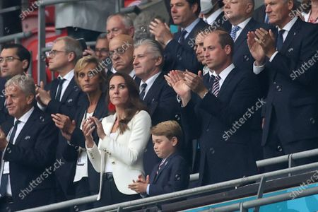 Britain's Prince William, foreground right, with his wife Kate and their son Prince George, center, applaud during the ceremony before the Euro 2020 soccer championship final match between England and Italy at Wembley stadium in London