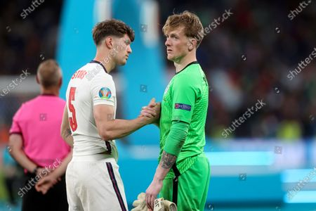 England's John Stones shakes hands with England's goalkeeper Jordan Pickford, right, at the end of the Euro 2020 soccer championship final match between England and Italy at Wembley stadium in London, . Italy defeated England 3-2 in a penalty shootout after the game ended in a 1-1 draw