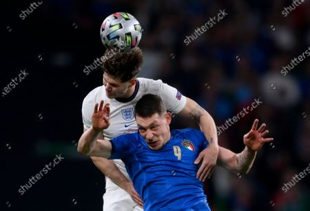 England's John Stones, background, and Italy's Andrea Belotti jump for the ball during the Euro 2020 soccer final match between England and Italy at Wembley stadium in London