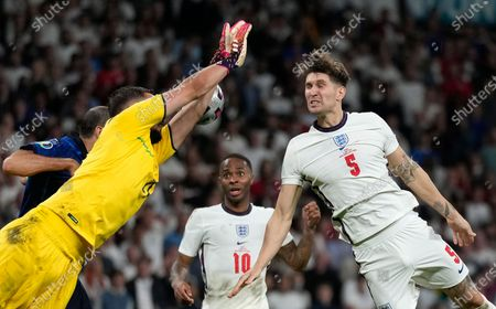 England's John Stones, right, and Italy's goalkeeper Gianluigi Donnarumma challenge for the ball during the Euro 2020 soccer championship final between England and Italy at Wembley stadium in London