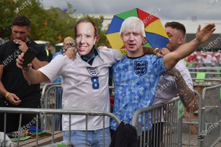 Stock Photo of English supporters wear masks of British Prime Minister Boris Johnson, right, and former Health Secretary Matt Hancock at a fan zone in Manchester, England, prior to the Euro 2020 soccer championship final match between England and Italy at Wembley Stadium in London