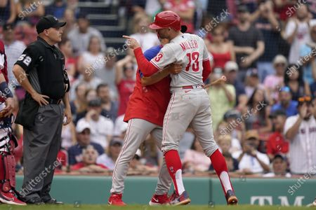 Philadelphia Phillies' Brad Miller, right, argues a call with umpire Jansen Visconti (52) as Phillies manager Joe Girardi, behind right, intervenes in the ninth inning of a baseball game against the Boston Red Sox, in Boston