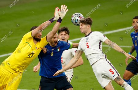 Italy's goalkeeper Gianluigi Donnarumma and England's John Stones compete for the ball during the Euro 2020 soccer championship final between England and Italy at Wembley stadium in London