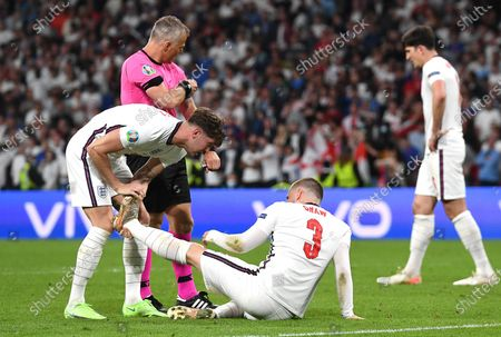 John Stones (L) of England stretches the leg of teammate Luke Shaw (C) during the UEFA EURO 2020 final between Italy and England in London, Britain, 11 July 2021.