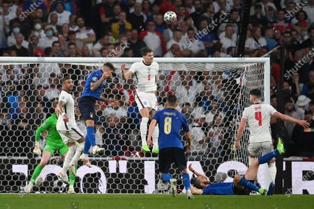 England's John Stones, top, heads the ball during the Euro 2020 soccer final match between England and Italy at Wembley stadium in London