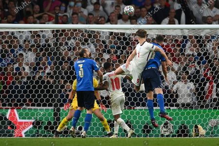 England's John Stones, second right, attempts a head at goal in front of Italy's Bryan Cristante during the Euro 2020 soccer final match between England and Italy at Wembley stadium in London
