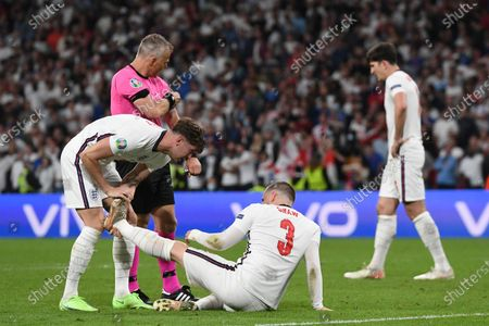 England's John Stones, left, stretches the leg of England's Luke Shaw during the Euro 2020 soccer final match between England and Italy at Wembley stadium in London