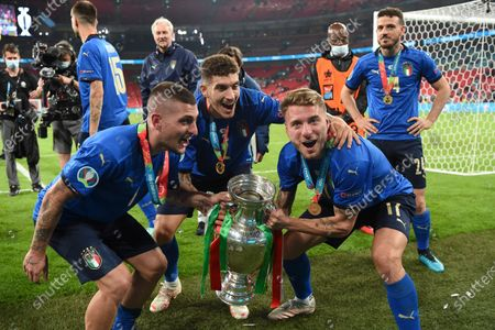 Italy's Marco Verratti, left, Italy's Giovanni Di Lorenzo, center, and Italy's Ciro Immobile celebrate with the trophy after the final of the Euro 2020 soccer final match between England and Italy at Wembley stadium in London