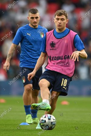 Italy's Nicolo Barella, right, and Italy's Marco Verratti warm up ahead of the Euro 2020 soccer final match between England and Italy at Wembley stadium in London