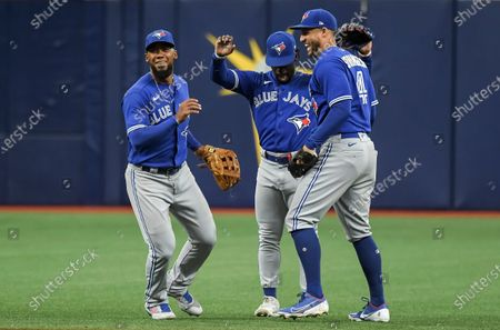 Toronto Blue Jays outfielders Teoscar Hernandez, from left to right, Jonathan Davis and George Springer celebrate a 3-1 win over the Tampa Bay Rays during a baseball game, in St. Petersburg, Fla