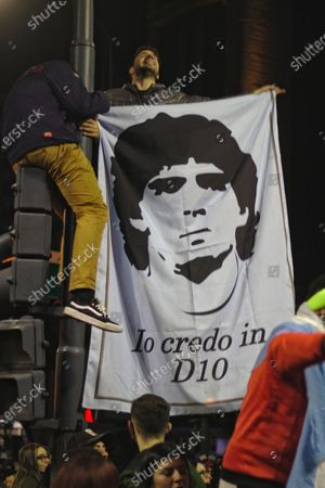 Fans of the Argentina team celebrating with a Diego Maradona poster.