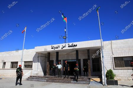 Officers stand guard outside Jordan's State Security Court, as it is set to announce its verdict in the trial of two officials accused of helping Prince Hamzah try to overthrow his half-brother King Abdullah II, in the capital Amman, Jordan, 12 July 2021. The court is to rule in the trial of two ex-officials accused of plotting a palace coup.