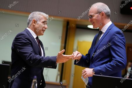 Israeli Foreign Minister Yair Lapid, left, speaks with Ireland's Foreign Minister Simon Coveney during a meeting of EU foreign ministers at the European Council building in Brussels on