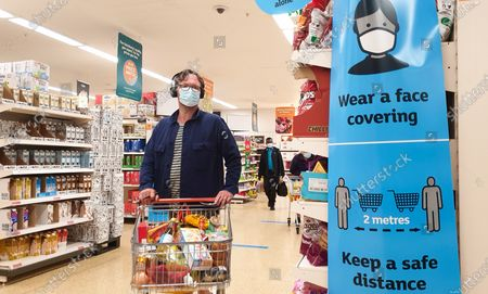 A shopper wearing a face covering walks past 'Wear a Face Covering' and 'Keep a safe distance' signs in a Sainsbury's supermarket in London. Prime Minister Boris Johnson will provide an update to step four of easing the Covid-19 lockdown in a press conference later today. It is expected that the face coverings in shops, pubs and mass events will no longer be mandatory after Freedom Day on 19 July. Businesses will be able to set rules for entry to their own premises. Vaccines Minister Nadhim Zahawi said that people will still be expected to wear a face covering in 'enclosed indoor spaces', though it will no longer be legal to do so.