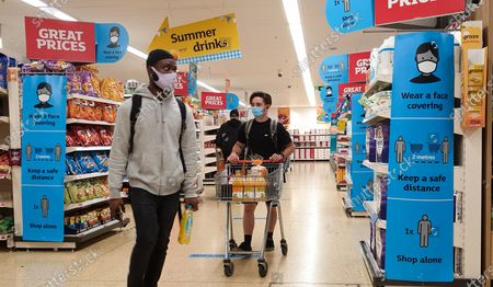 Shoppers wearing face coverings walk past 'Wear a Face Covering' and 'Keep a safe distance' signs in a Sainsbury's supermarket in London. Prime Minister Boris Johnson will provide an update to step four of easing the Covid-19 lockdown in a press conference later today. It is expected that the face coverings in shops, pubs and mass events will no longer be mandatory after Freedom Day on 19 July. Businesses will be able to set rules for entry to their own premises. Vaccines Minister Nadhim Zahawi said that people will still be expected to wear a face covering in 'enclosed indoor spaces', though it will no longer be legal to do so.
