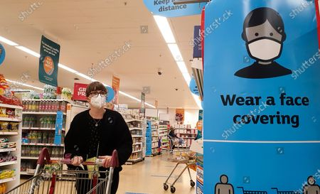 Stock Image of A shopper wearing a face covering walks past 'Wear a Face Covering' and 'Keep a safe distance' signs in a Sainsbury's supermarket in London. Prime Minister Boris Johnson will provide an update to step four of easing the Covid-19 lockdown in a press conference later today. It is expected that the face coverings in shops, pubs and mass events will no longer be mandatory after Freedom Day on 19 July. Businesses will be able to set rules for entry to their own premises. Vaccines Minister Nadhim Zahawi said that people will still be expected to wear a face covering in 'enclosed indoor spaces', though it will no longer be legal to do so.