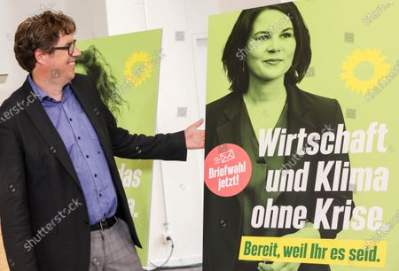 Michael Kellner, party secretary of the German Greens Party (Die Gruenen) poses next to a new Green party election poster showing Green party co-chairwoman and top candidate for the upcoming federal elections, Annalena Baerbock, during a press conference in Berlin, Germany, 12 July 2021. Michael Kellner presented the Green Party campaign for the 2021 German federal election.