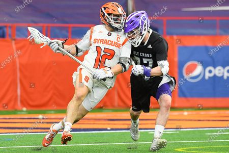 Syracuse Orange midfielder Jamie Trimboli (12) dodges to the goal against the defense of Holy Cross Crusaders midfielder Peter Murphy (77) during the second half of an NCAA mens lacrosse game on Saturday, March, 20, at the Carrier Dome in Syracuse, New York. Syracuse won 15-6