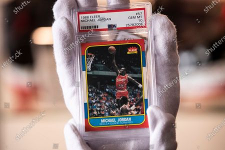 Michael Jordan 1986 fleer rookie card #57 is held by an employee during the preview of the auction 'Sports Legends' at Julien's auction in Beverly Hills, California, USA, 12 July 2021. The auction will take place on July 17 and 18, 2021.