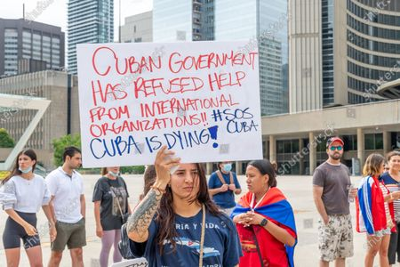 Stock Image of Members of the Cuban community in Toronto, Canada demonstrate in support of the protests for change in the Caribbean island. They are also demanding change in Cuba and the end of communism. The event takes place in Nathan Phillips Square.