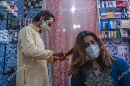 A Kashmiri transgender gets her hair done at a beauty parlor by another transgender before attending a marriage function in Srinagar, the summer capital of Indian Kashmir, 09 July 2021 (issued 13 July 2021). Kashmiri transgender people, who work as matchmakers, sing and dance at marriage functions, and at beauty parlors, have been living from hand-to-mouth due to COVID-19 lockdowns. According to them, they are suffering due to no work as the marriage seasons got badly hit in Kashmir, forcing them to work as manual laborers. They say that while certain NGOs have come out to help some of them, the support has not been adequate.