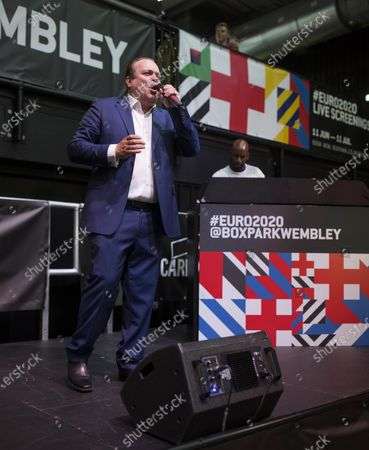 Stock Image of Shaun Williamson best known as Barry from Eastenders, sings Sweet Caroline, Mustang Sally and Something Inside So Strong at Boxpark Wembley before England's game against Ukraine at Euro 2020 which took place in Rome. DJ Spoony can be seen in the background.