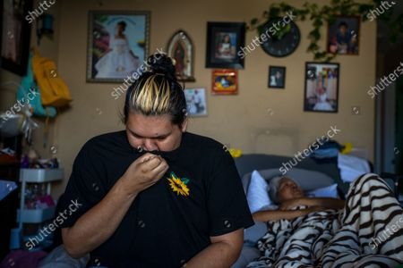 Sandy Vazquez, 30, left, cries as she sits on a fold out bed next to her mother Reyna Chautla, in their living room on Friday, June 11, 2021 in South Los Angeles, CA. Sandy begins to tear up as she listens as her mother begins to cry. (Francine Orr / Los Angeles Times)